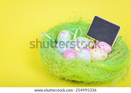 Easter eggs in nest with copy-space blackboard over yellow paper - stock photo