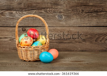Easter eggs in the basket of wooden table. - stock photo