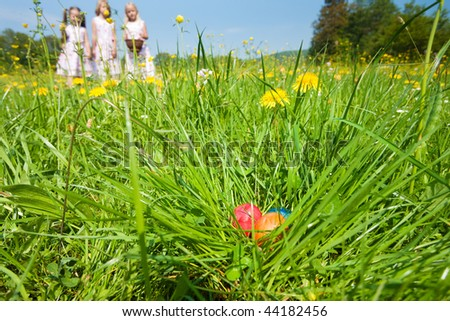 Easter eggs in the grass waiting to be found by children who are already on the hunt - stock photo