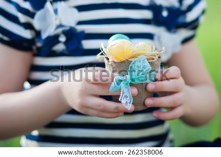Easter eggs in the hands of a child - stock photo