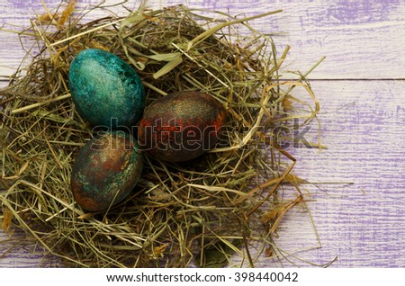 Easter eggs in the nest on wooden background.Rustic style.