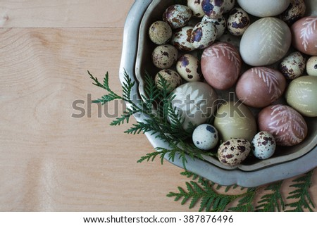 Easter eggs in vintage bowl on wooden planks, dyed with natural dyes - stock photo