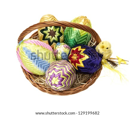 Easter eggs in wicker basket  on white background.
