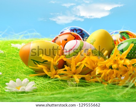 Easter eggs laying in green grass with daisy under blue sky