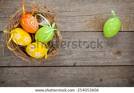 Easter eggs nest over wooden table background - stock photo
