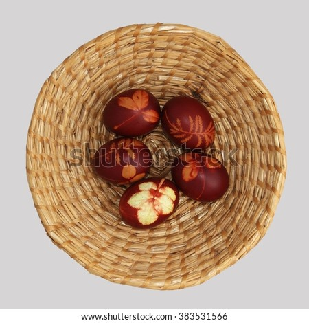 Easter eggs on a basket - in a traditional rustic style. Isolated.