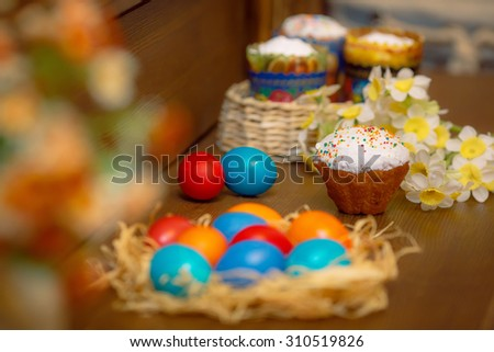 Easter eggs on a wooden background with a straw - stock photo