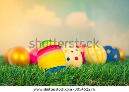 Easter Eggs on Fresh Green Grass over blue sky ( Filtered image processed vintage effect. ) - stock photo