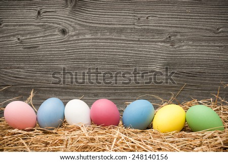 Easter eggs on old wooden background with copy space for your message - stock photo