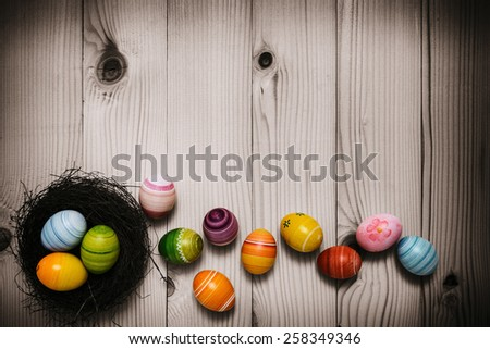Easter eggs on wooden background -Hand painted colorful Easter eggs on rustic wooden planks - stock photo