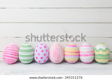 Easter eggs painted in pastel colors on white wooden background. Easter concept - stock photo