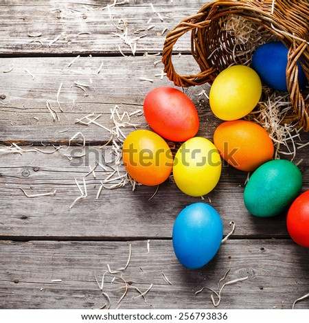 easter eggs scattered near braided basket on wooden background. Left side is designed for text - stock photo