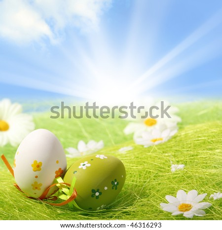 Easter Eggs sitting on grass field with blue sky background - stock photo