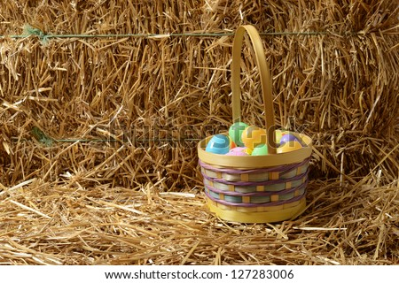 Easter eggs with basket and straw - stock photo