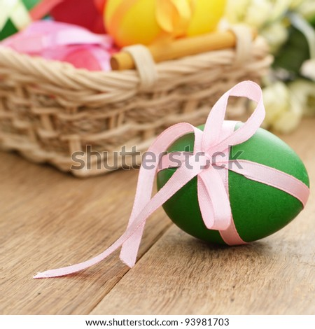 Easter eggs with bows in the basket over floral background - stock photo