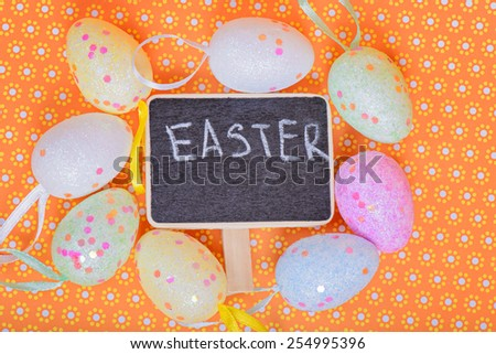 Easter eggs with chalkboard with copy-space over orange floral background - stock photo