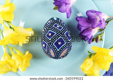 Easter eggs with flowers on plate close up - stock photo