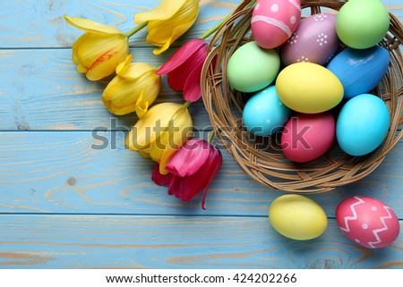 Easter eggs with tulips on a blue wooden table - stock photo