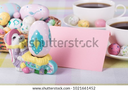 Easter figurine and egg and blank envelope with cups of coffee and Easter basket in background