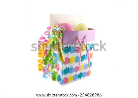 Easter gift bag with card, eggs, and decorative ribbon. - stock photo