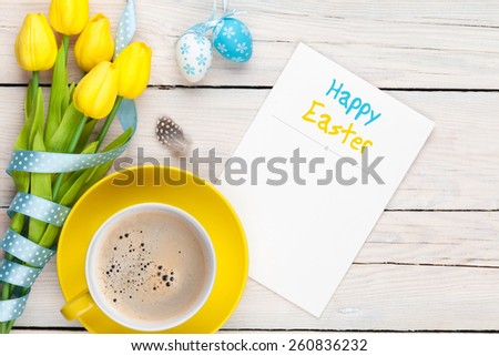 Easter greeting card with blue and white eggs, yellow tulips and coffee cup over white wood. Top view with copy space  - stock photo
