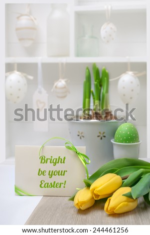 Easter greeting card with green ribbon, yellow tulips and daffodil sprouts with decorated shadowbox as the backdrop. Shallow DOF, focus on the ribbon, bow and text. - stock photo