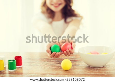 easter, holiday and child concept - close up of little girl holding colored eggs with colors and bowl on the table - stock photo