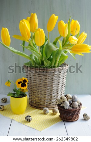 Easter holiday composition with yellow tulips on wooden table over retro background - stock photo
