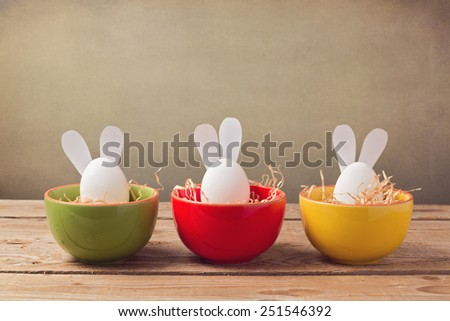 Easter holiday eggs with bunny ears on wooden table - stock photo
