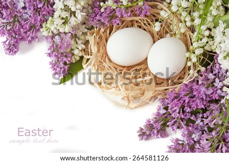 Easter holiday (still life with eggs in nest and lilac flowers isolated on white background with sample text). Easter symbol - stock photo