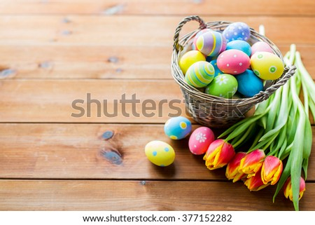 easter, holidays, tradition and object concept - close up of colored easter eggs in basket and tulip flowers on wooden table with copy space - stock photo