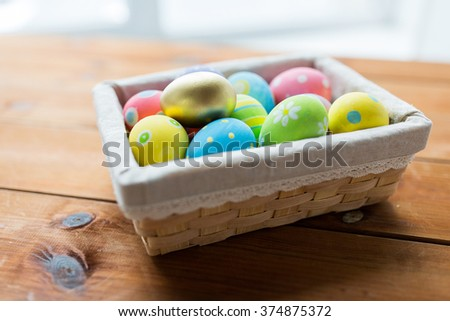 easter, holidays, tradition and object concept - close up of colored easter eggs in wicker basket - stock photo