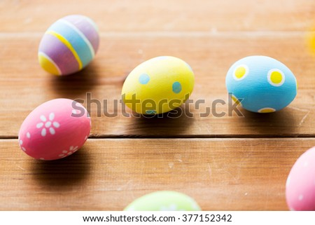 easter, holidays, tradition and object concept - close up of colored easter eggs on wooden surface - stock photo