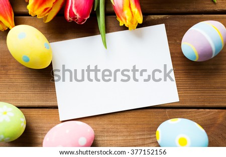 easter, holidays, tradition and object concept - close up of colored easter eggs, tulip flowers and blank white paper card on wooden surface with copy space - stock photo