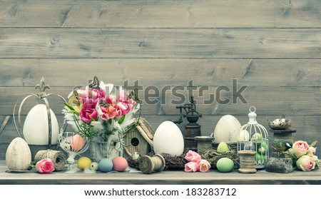 Easter home interior decoration with pink tulip flowers and colored eggs. Shabby chic. Vintage style toned picture - stock photo