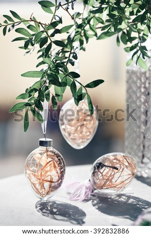 Easter interior with glass egg decorations, green leaves branch, feathers beside window. Natural light photo. Modern simple decoration style concept. Toned photo. - stock photo