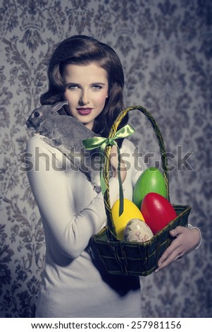 easter lovely portrait of brunette woman with retro hair-style posing with colorful eggs in cheerful basket and tender rabbit on her shoulder  - stock photo
