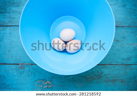 Easter - natural white eggs in a blue bowl on an old vintage planked wood table. Rural or rustic kitchen still life - stock photo