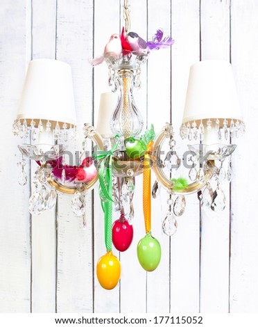 Easter or spring home interior decorations - vintage crystal chandelier with colorful birds, ribbons and eggs. - stock photo