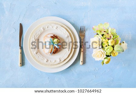 Easter or wedding place setting with sweet pie on a plate on blue colors.