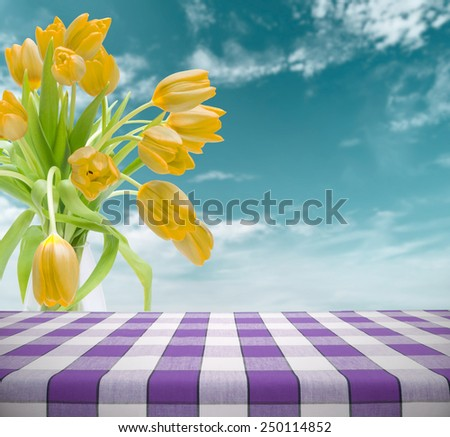 Easter picnic table template with yellow tulips against cloudy sky in background - stock photo