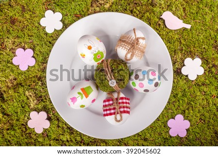 Easter plate, eggs and decoration on green moss backround