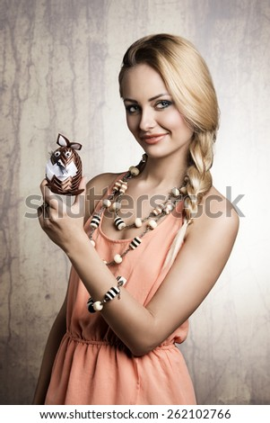 easter portrait of sexy blonde female with spring dress and jewellery showing funny small stuffed bunny toy - stock photo