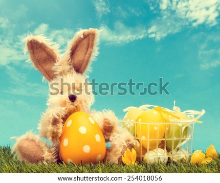 Easter Rabbit in grass with easter eggs in basket, retro toned - stock photo