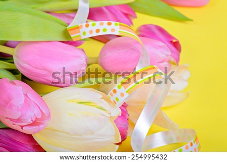 Easter ribbon with pink tulips over yellow paper - stock photo