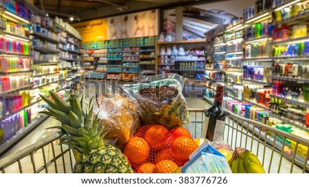 Easter shopping Grocery cart at a colorful supermarket filled up with food products as seen from the customers point of view - stock photo