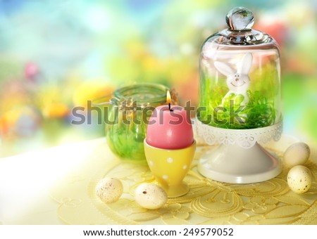 Easter table decor with rabbit, candle, easter eggs - stock photo