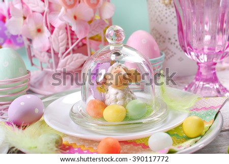 easter table decoration in pastel colors with lamb and candy eggs in glass ball - stock photo