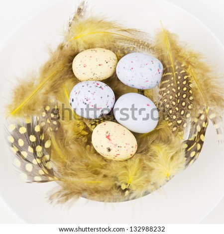 Easter table setting for a festive dinner - a decorative yellow nest with colourful ester eggs on a plate - stock photo