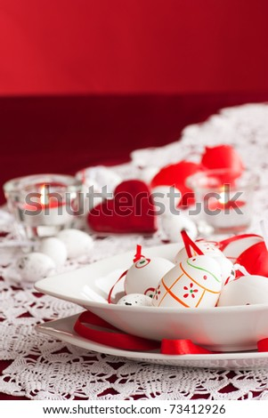 Easter table setting in red tones with candles and flower. Available space for your text.